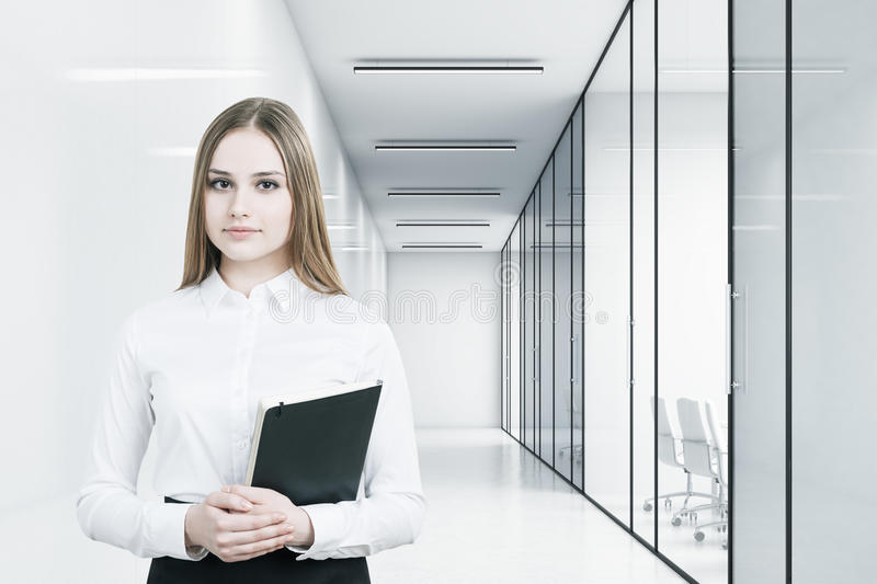Young girl in an office suit is holding a black folder and standing in a white office corridor with conference rooms. 3d rendering. Mock up vector illustration