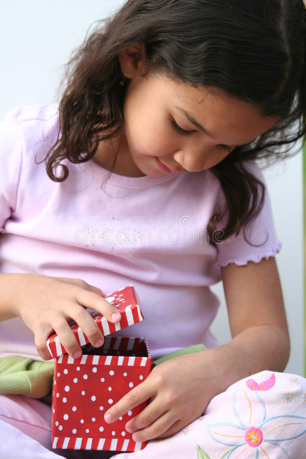 Young Girl Opening Present stock photos