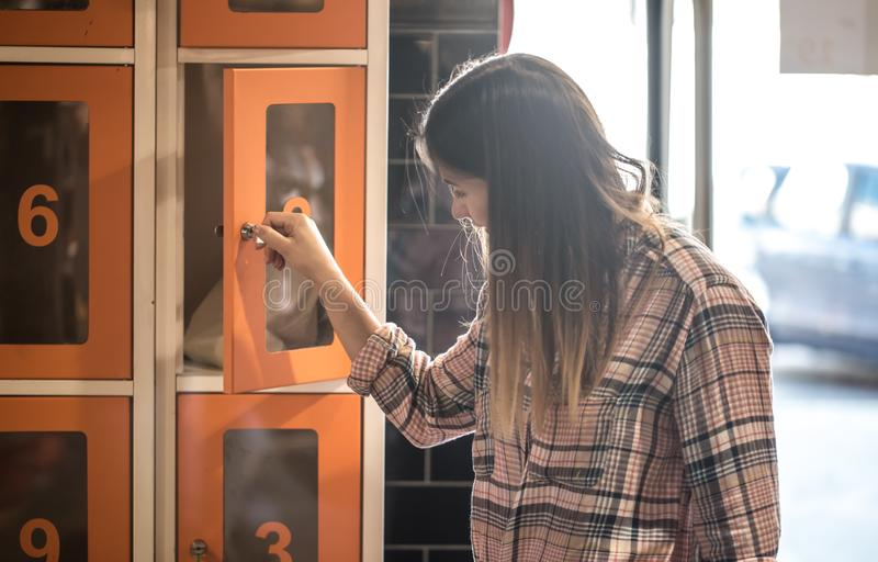 Girl opens a locker in the store and puts the eco bag. A young girl opens a locker in the store and puts the eco bag royalty free stock photography