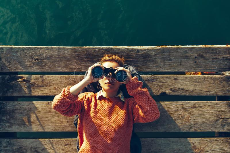 Young Girl Lies On A Pier Near The Sea And Looks Through Binoculars. Travel Search Journey Concept royalty free stock photography