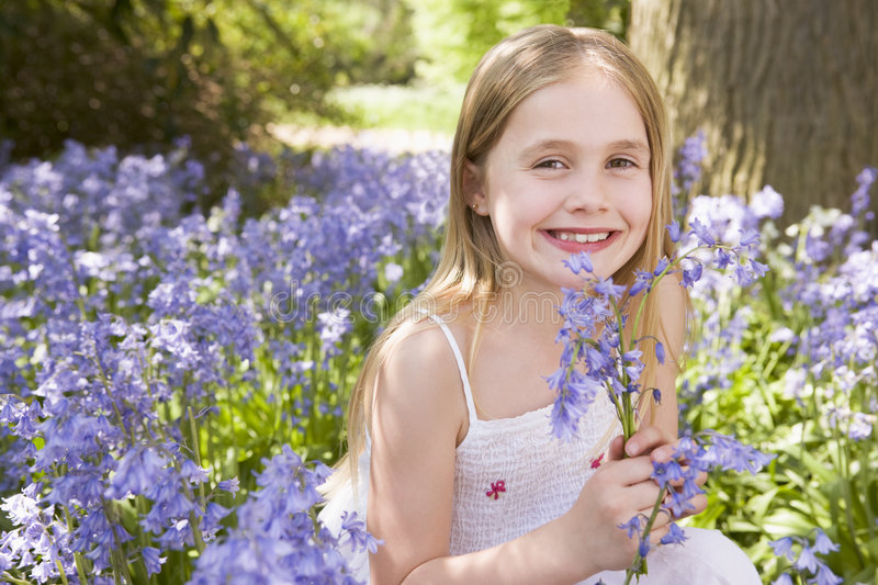 Young Girl Outdoors Holding Flowers Smiling Royalty Free Stock Photos