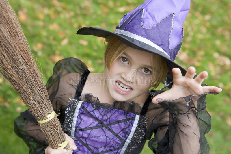 Young girl outdoors in witch costume on Halloween stock photos