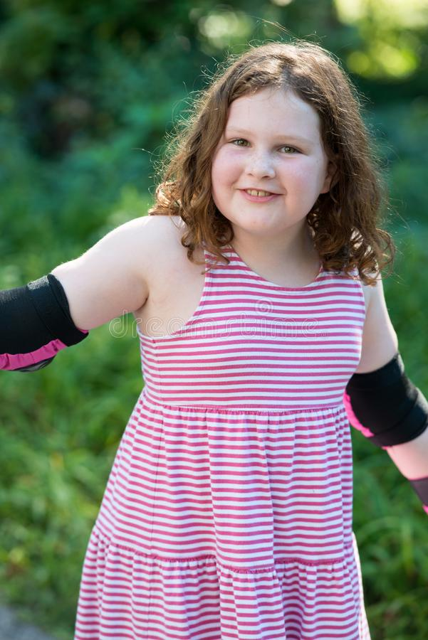 Young girl outside learning to riding on roller skates on driveway wearing protective elbow, wrist and knee pads stock image
