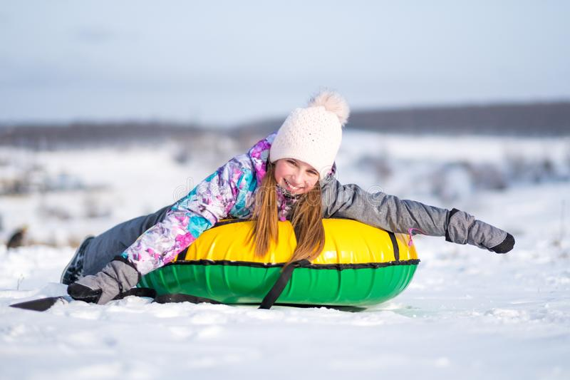 Little girl enjoying snow tubing at sunny weather. Young girl outstretched her arms while enjoying snow tubing at sunny winter weather stock photo