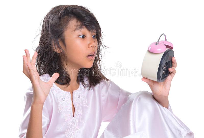 Young Girl Overslept I. Concept image of overslept young girl checking the time with her alarm clock stock images