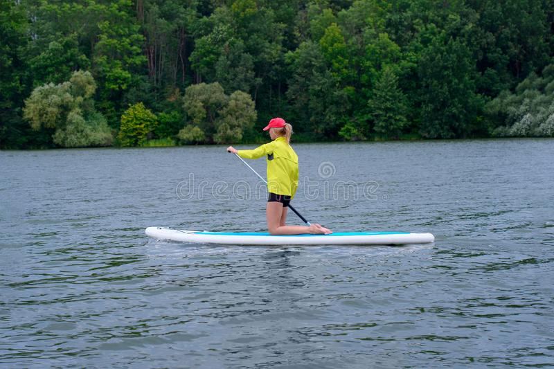 Young girl paddling on SUP board on a calm lake at city. Sup surfing woman. Awesome active training in outdoor stock photo