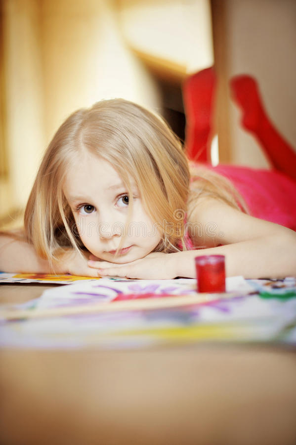 Young girl painting. A young girl laying on the floor painting stock image