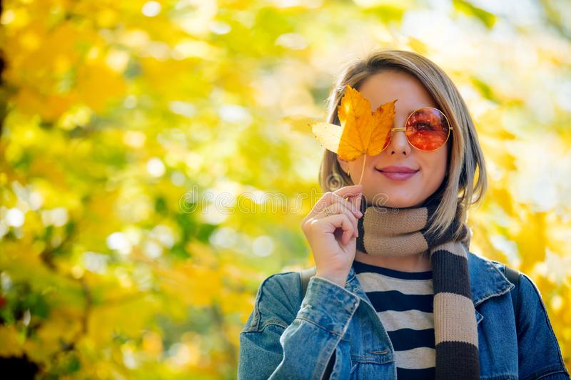 Young girl in the park in autumn season time. Young beautiful blonde girl in blue jeans clothes have rest in the park in autumn season time royalty free stock image