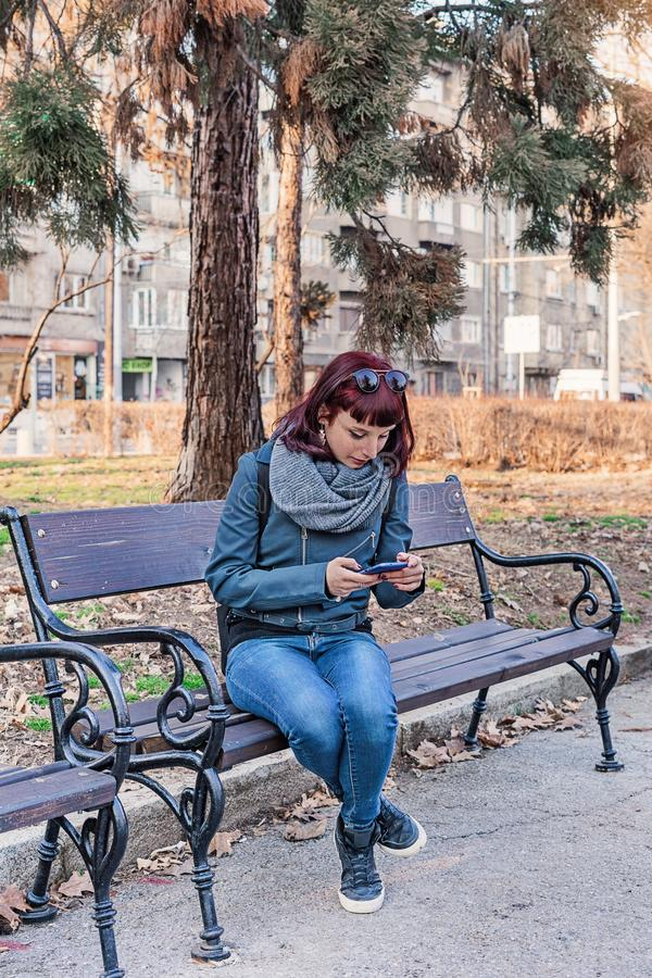 Young girl in the park texting on the phone and waiting stock image