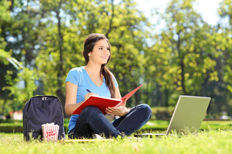 Download Young Girl In Park Writing In A Notebook Stock Photo - Image: 39321776