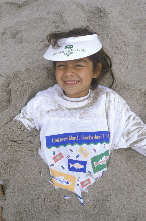 A young girl partially covered by sand stock image
