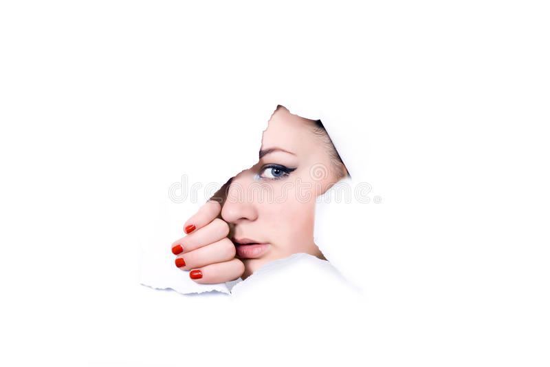 Young girl peeping through hole in paper royalty free stock image