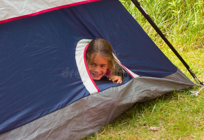 A young girl peering through an opening in a nylon tent. A youngster having fun in the family tent at an ontario campground in the summertime royalty free stock photos