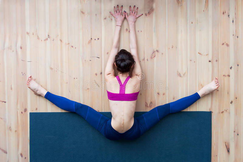 Young girl performing wide-angle seated forward bend or upavistha konasana during stretching class in gym stock image