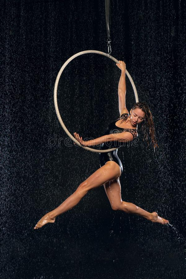 A young girl performs the acrobatic elements in the aerial ring. Aqua Studio shooting performances on a black background stock image