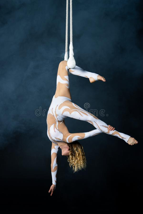 A young girl performs the acrobatic elements in the air trapeze. Studio shooting performances on a black background.  royalty free stock photography