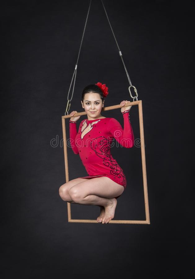 Aerial acrobat in the trapeze. A young girl performs the acrobatic elements in the air trapeze. Studio shooting performances on a black background royalty free stock photography