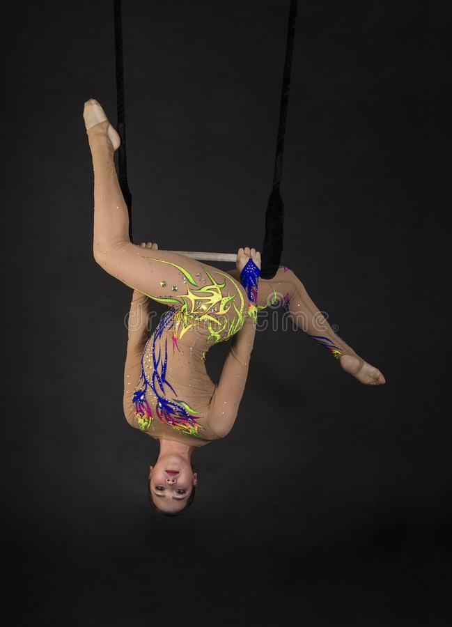 Aerial acrobat in the trapeze. A young girl performs the acrobatic elements in the air trapeze. Studio shooting performances on a black background royalty free stock image