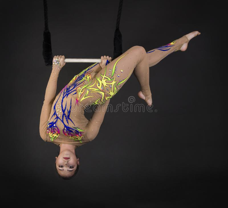 Aerial acrobat in the trapeze. A young girl performs the acrobatic elements in the air trapeze. Studio shooting performances on a black background royalty free stock photos