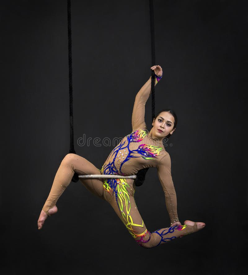Aerial acrobat in the trapeze. A young girl performs the acrobatic elements in the air trapeze. Studio shooting performances on a black background stock images