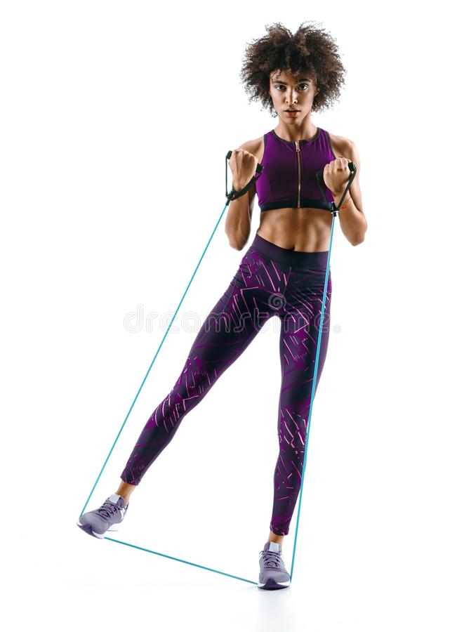 Young girl performs exercises using expander on white background stock images