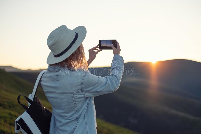 Young girl with a phone camera in the mountains during sunset. Girl and phone. Photographing landscapes by phone. royalty free stock photos