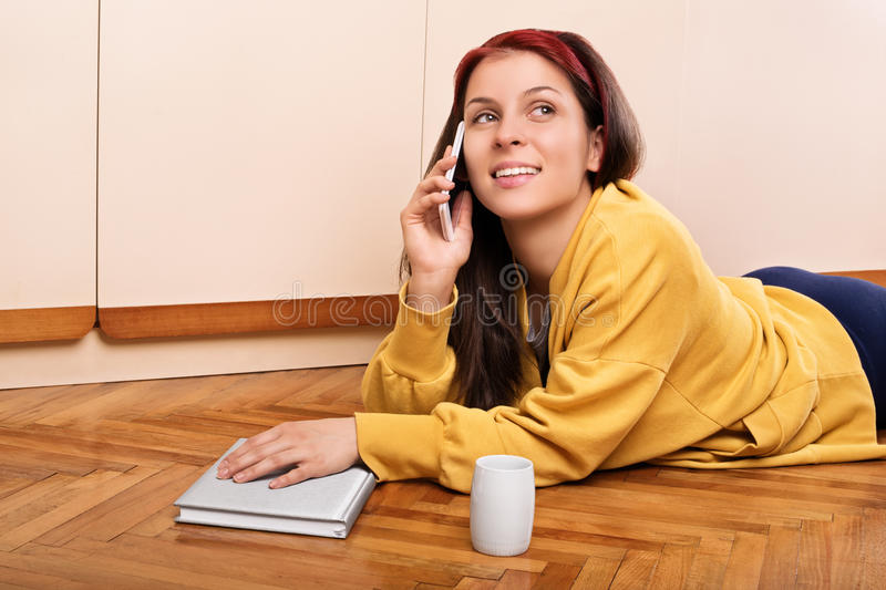 Young girl on the phone lying on the floor with a book and a cup. Let me tell you what a fine book I just finished reading. Young girl on the phone talking about royalty free stock photos