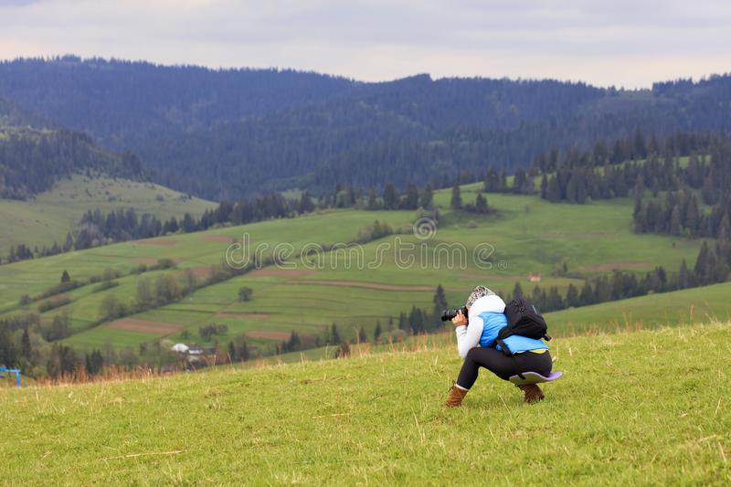 A photographer half crouching shoots the landscape of the Carpathian slopes on a fresh spring morning royalty free stock images