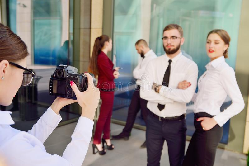 Young girl photographes colleagues in the background of an office building. royalty free stock photos