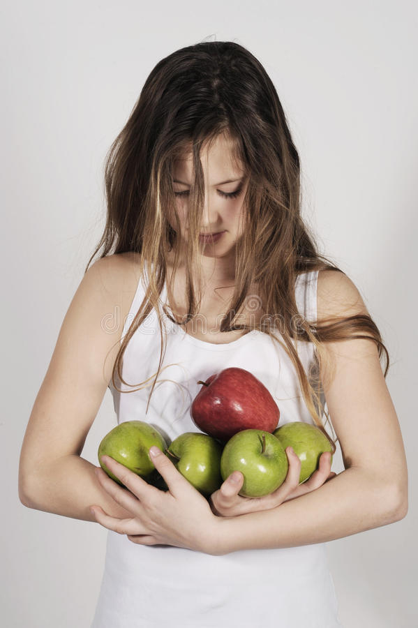 Young girl with a pile of apples stock images