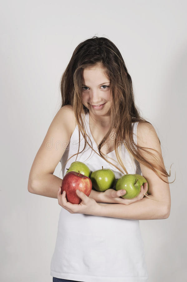 Young girl with a pile of apples stock photos