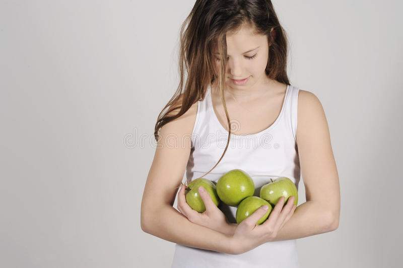 Young girl with a pile of apples royalty free stock photography
