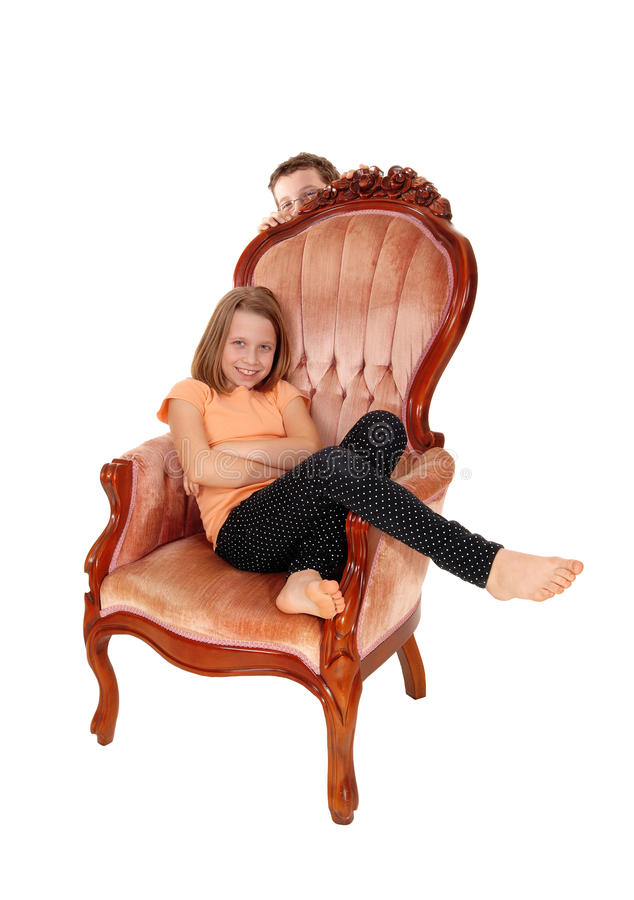 Young girl in pink armchair. A very pretty young girl sitting in a pink armchair, isolated for white background stock images