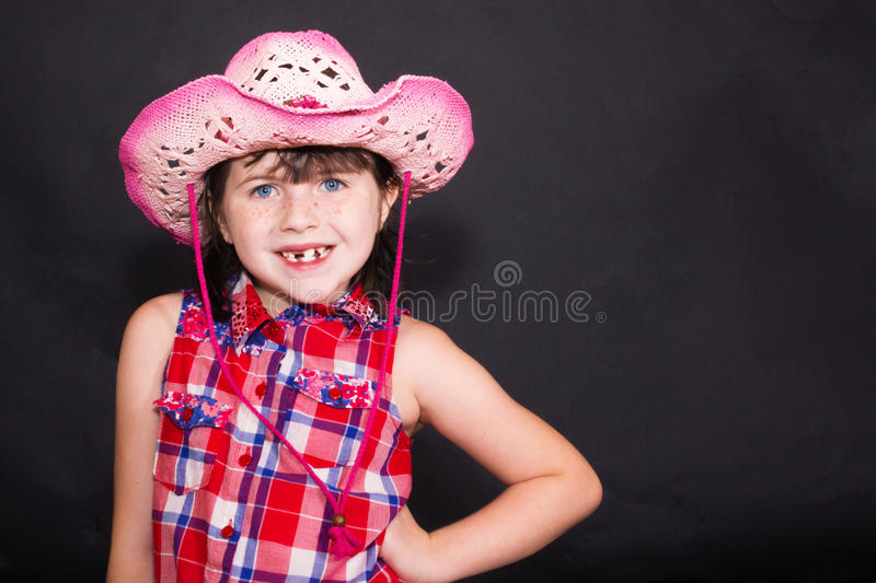 Young Girl in a Pink Cowboy / Cowgirl Hat Black Ba. Young girl in a pink cowboy cowgirl hat with black background. Wearing plaid shirt royalty free stock images