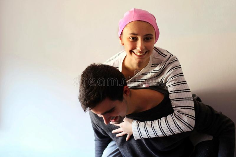 Young girl with pink handkerchief on her head on top of her husband. Concept of breast cancer patients stock photos