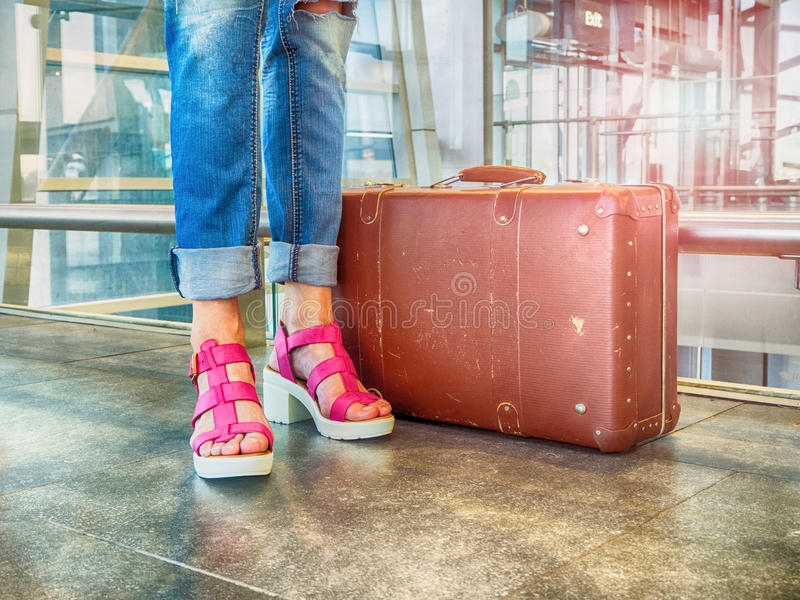 Young girl in pink shoes in the lobby with vintage luggage airport awaiting my flight. Photo in retro style. The concept on stock images