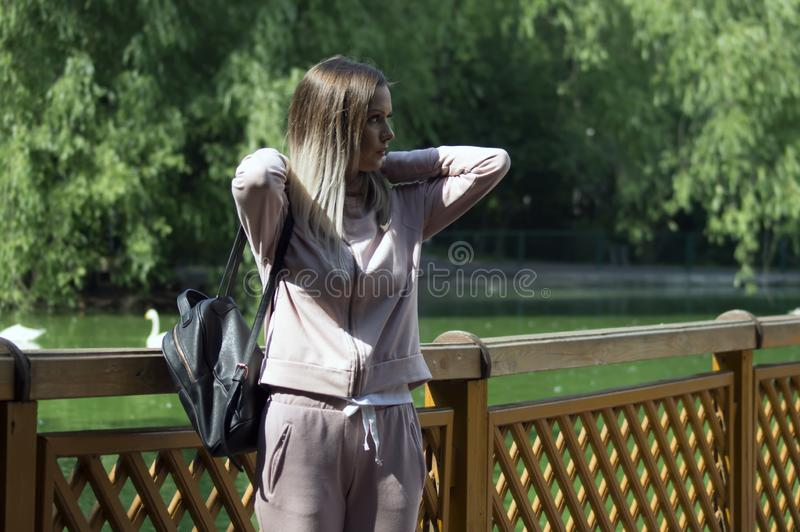 A young girl in a pink sports suit travels. To the Zoological Park stock photo