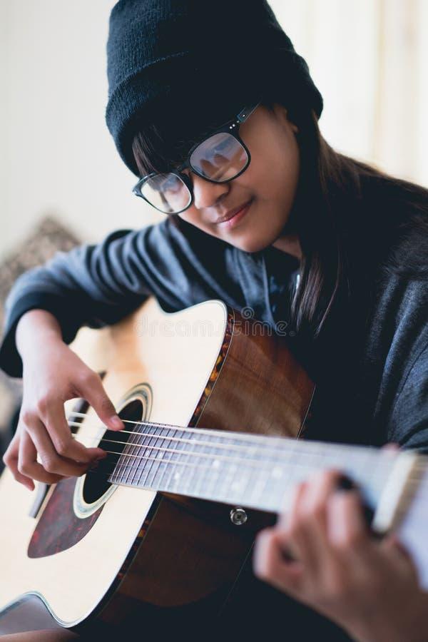 Young girl play guitar. Closeup young asian girl play acoustic guitar stock image