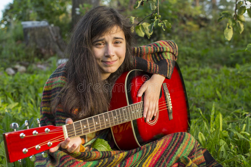 Young girl playing acoustic guitar royalty free stock image