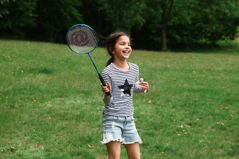 Girl playing badminton in the park. stock image