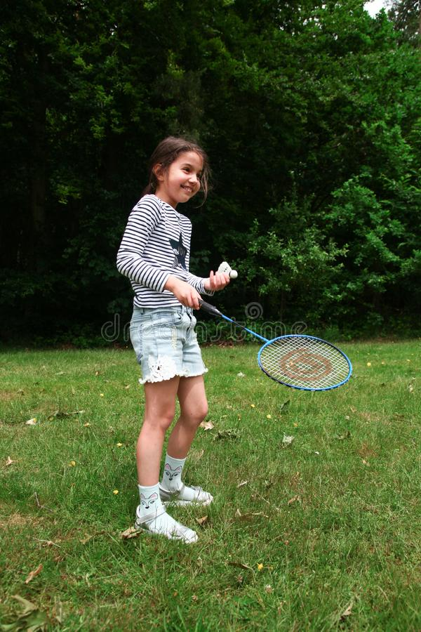 Girl playing badminton in the park. stock photography