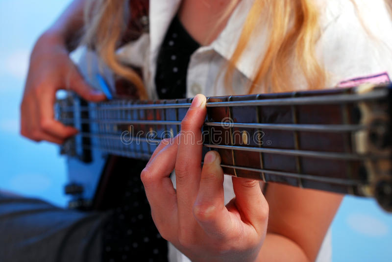 Young girl playing bass guitar on the stage royalty free stock images