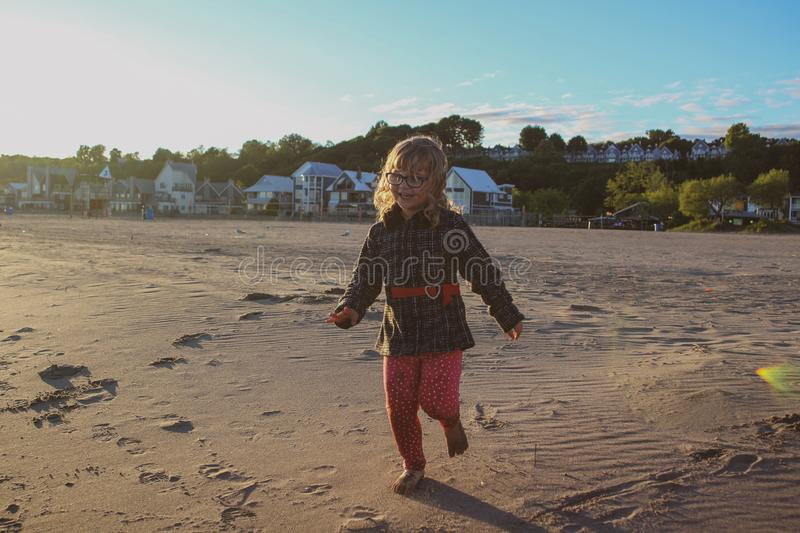 Young girl playing on the beach running and having a joyful time royalty free stock photos