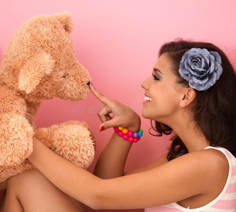 Young girl playing with big teddy bear royalty free stock photography