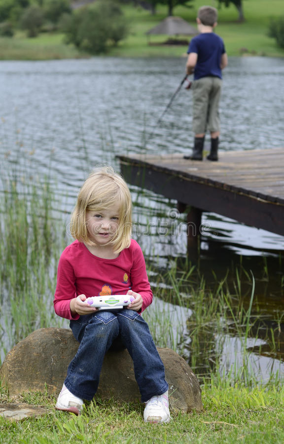 Young girl playing computer game in nature stock photo