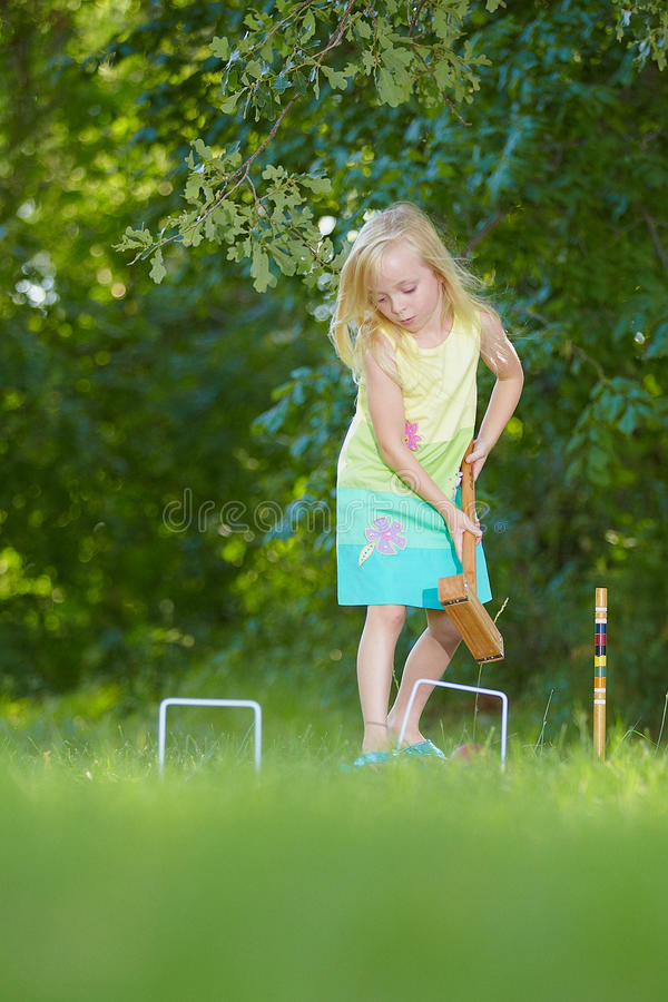 Young girl playing croquet. Young blond haired girl playing croquet on grass with leafy trees in background royalty free stock image