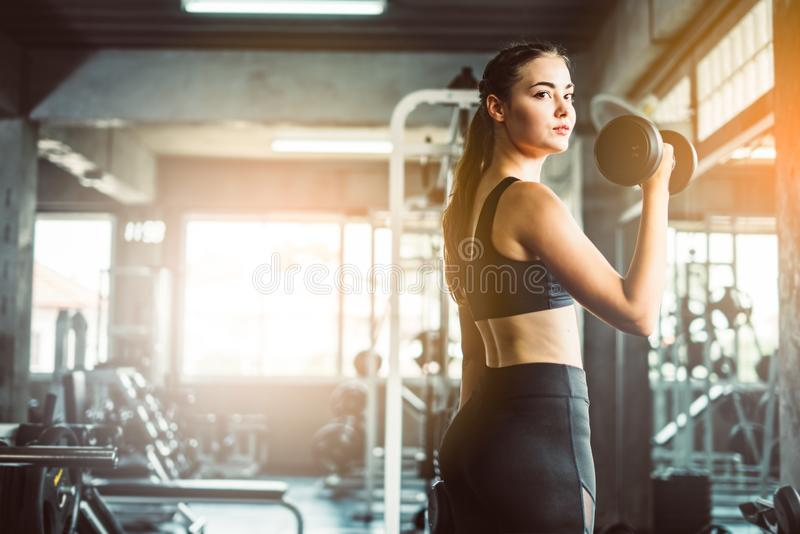 Young girl playing dumbbell to exercise in fitness.Slim girl lifts heavy dumbbell while training in the gym. Sports concept fat b stock photo