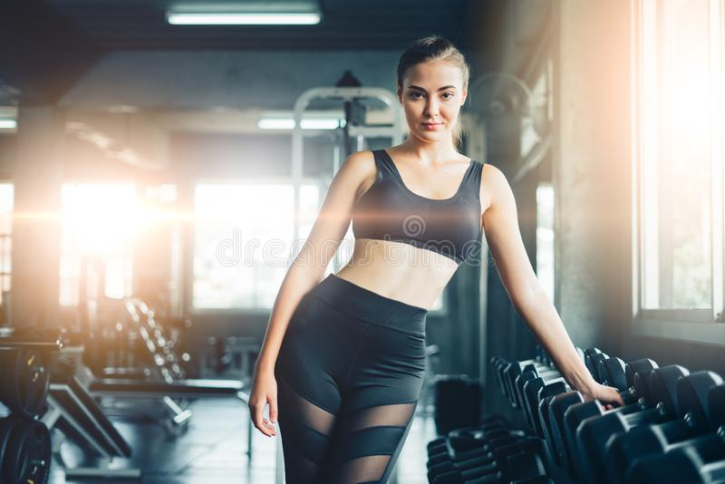 Young girl playing dumbbell to exercise in fitness.Slim girl lifts heavy dumbbell while training in the gym. Sports concept fat b royalty free stock photo
