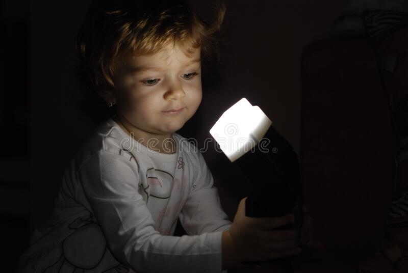 Young girl playing with flashlight. A portrait of a young girl playing with a flashlight in the dark stock photos