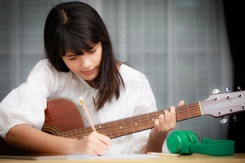 Young girl playing guitar and compose music royalty free stock image